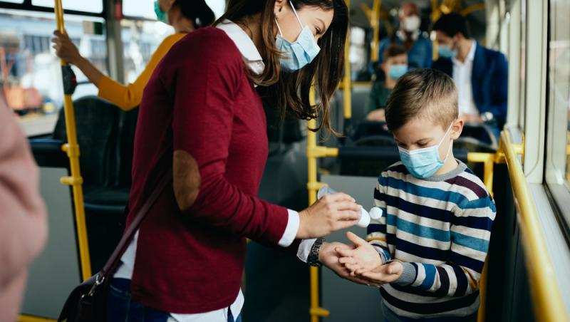 femeie si copil in autobuz cu mastile puse si se dau cu dezinfectant