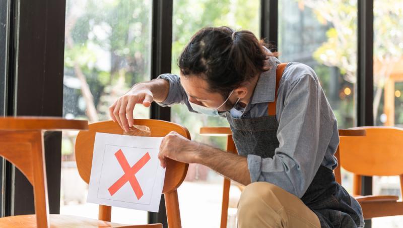 barbat care lipeste o foaie alba cu x pe un scaun