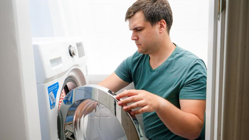 barbat deschizand masina de spalat