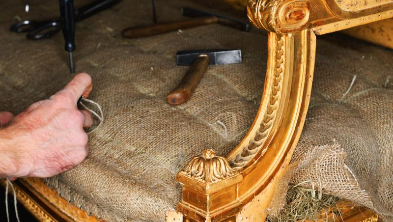 imagine cu un barbat reparand o canapea