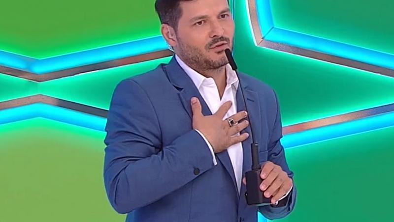 Liviu Vârciu în costum albastru la Prețul cel bun, vorbește la microfon