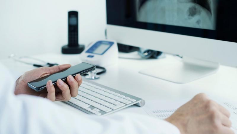 imagine cu un telefon tinut in mana de un medic ce analizeaza o ecografie