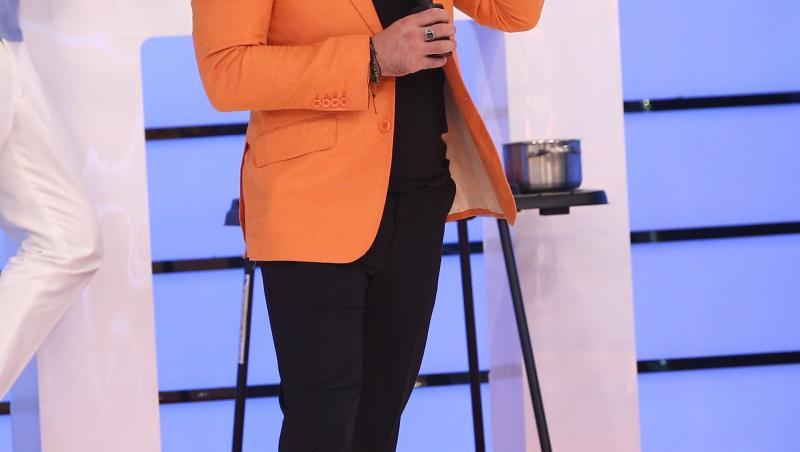 Liviu Vârciu în sacou portocaliu și tricou negru, vorbește la microfon