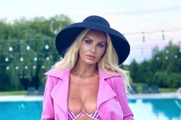 Andreea Bănică într-un sacou roz și sutien roz, iar pe cap are o pălărie neagră