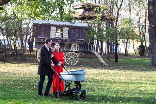 Fostul Principe Nicolae, purtând sacou negru, împreună cu soția lui Alina Binder, purtând o rochie roșie și cu fetița lor, în cărucior