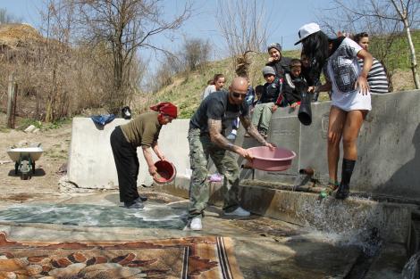 Margherita din Clejani și Giani Kiriță se bat cu apă în timp ce spală un covor