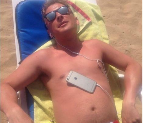 Imagini virale! A adormit cu telefonul pe piept la plajă. Ce s-a întâmplat cu bărbatul după întrece orice imaginaţie