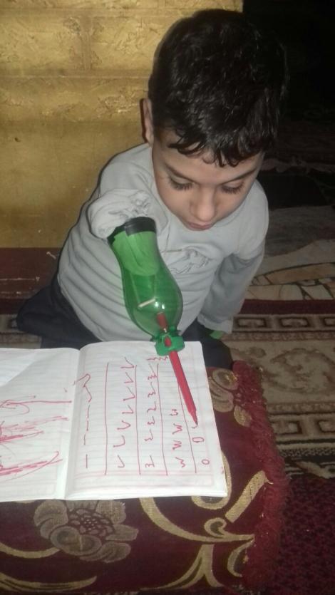 Așa arată o mânuță de om cu un munte de ambiție! Ziad învață să scrie folosind sticle de plastic, fiindcă nu are bani de proteze!