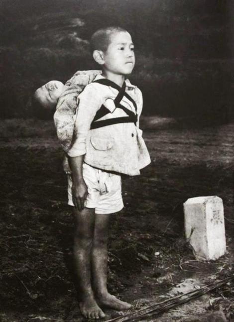 """Fotografia ce a cutremurat lumea! Băiețelul de 10 ani care-și duce în spate frățiorul, mort, la crematoriu. """"A așteptat să fie ars. Ca să nu plângă, și-a mușcat, până la sânge, buza!"""""""
