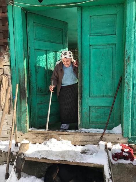 Imagini emoționante! Bătrâni izolați de nămeți, rămași fără hrană, ajutați de pompieri și polițiști. Au ajuns la ei cu șenilatele