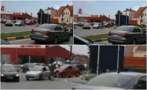 Doi șoferi nervoși și-au oprit mașinile în mijlocul unei intersecții aglomerate și s-au luat la bătaie