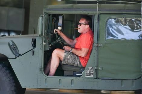 Arnold Schwarzenegger, fotografiat de paparazzi la bordul unui Hummer. Actrorul are trabuc în gură și este îmbrăcat într-un tricou roșu și pantaloni scurți