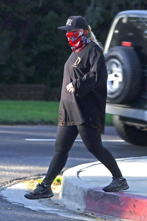 Rebel Wilson, îmbrăcată într-o ținută închisă la culoare, cu ochelari, șapcă și mască de protecție