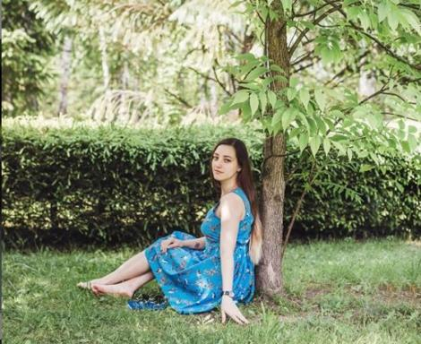 elena stand pe iarba, intr-o rochie inflorata