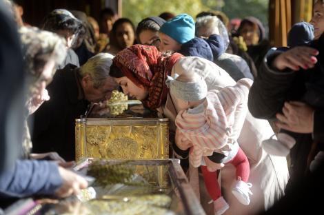 credinciosi care se inchina la moaste intr-o boserica ortodoxa