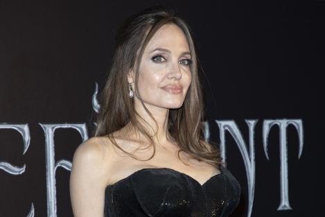 Angelina Jolie, fotografiata la o gala, unde poarta o tinuta neagra si este aranjata de stilisti