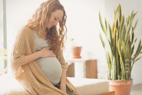 Femeie însărcinată, care privește cu dragoste către fătul nenăscut