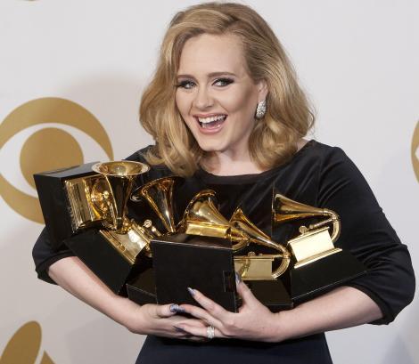Adele ține în brațe trofeele câștigate la gala de decernare a premiilor Grammy în anul 2012
