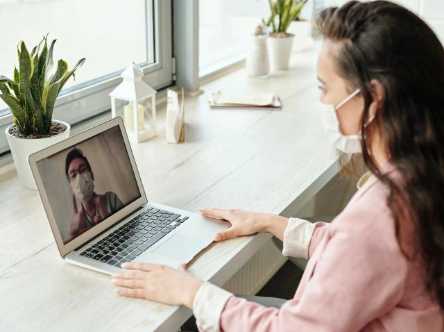 Femeie cu masca si bluza roz, sta in fata unul laptop deschis