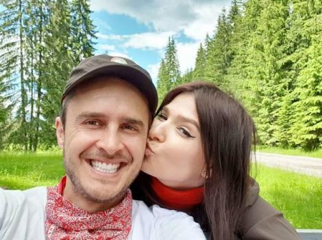 Șerban Copoț, cu o șapcă pe cap, zâmbește în timp ce soția îlsărută pe obraz