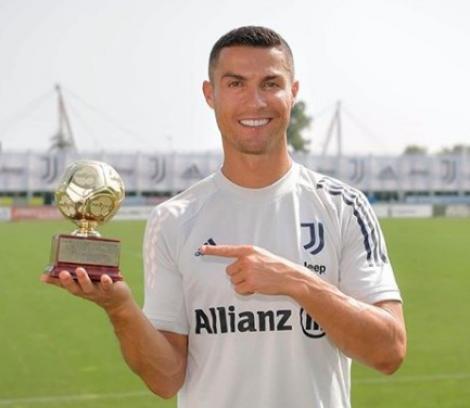 Cristiano Ronaldo pe terenul de fotbal, îmbrăcat într-un tricou alb, ține în mână un trofeu și zâmbește
