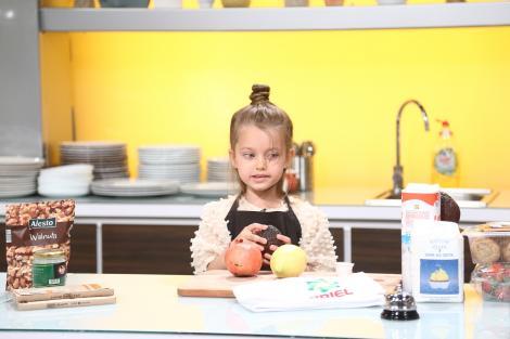 Anastasia în bucătarie, imbrăcată cu o bluză bej și un șorț negru, se pregătește să gătească, având pe masă fructe, făină și lapte.