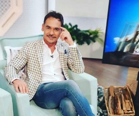 Răzvan Simion stă pe un fotoliu, îmbrăcat într-o cămașă albă, blugi albaștri și adidași albi.