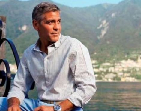 George Clooney într-o camasă albă, cu blugi albastri și ceas la mana.