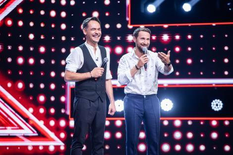 Răzvan Simion și Dani Oțil pe scena X-Factor, vorbesc la microfon, îmbbrăcați cu cămăși albe.