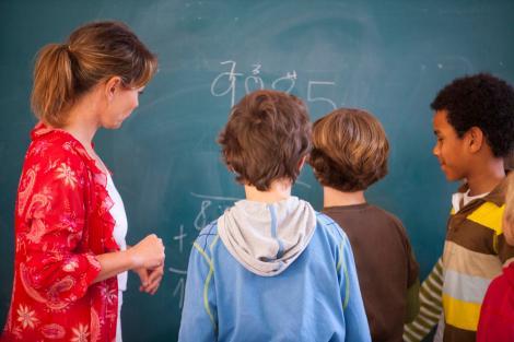 profesoara imbracata in rosu explica exercitii de matematica unor copii, in fata tablei