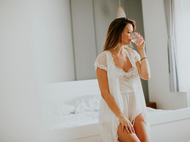 femeie imbracata in furou bea apa in dormitor