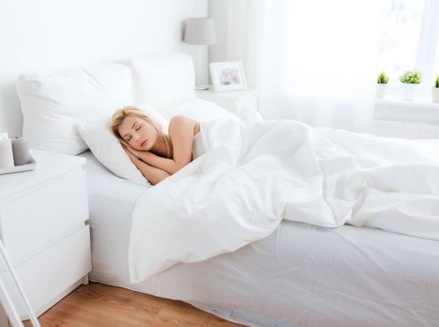 femeie care doarme intr-un pat cu asternuturi albe