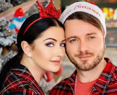 Tavi Clona și Gabriela Cristea de Craciun, îmbracați în bluze roși cu dungi verzi. Ea are pe cap o bentiță roșie cu fundiță, iar el o căciulă de moș crăciun.