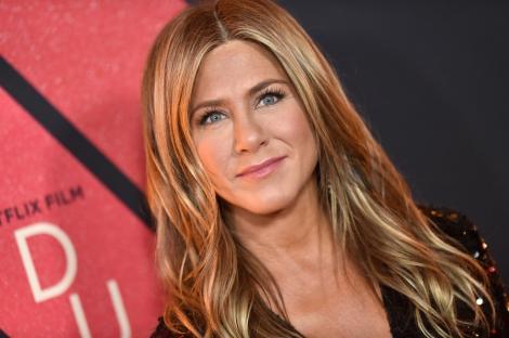 Jennifer Aniston pe covorul roșu, cu parul desfacut de culoare blond, are ochii albastri și este îmbrăcată într-o bluză neagră