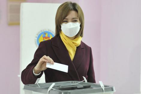 Maia Sandu, votând la al doilea tur al alegerilor prezidențiale din Republica Moldova, din 2020. Candidata proeropeană a purtat un palton vișiniu și o eșarfă galbenă