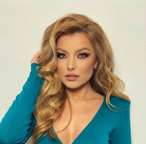 Elena Gheorghe imbracata intr-o bluza turcoaz, isi tine mana in parul buclat si priveste spre camera.