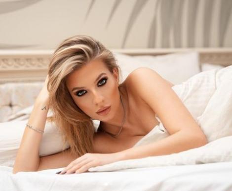 Ana Baniciu în pat, cu parul pe o parte, machiata strident.