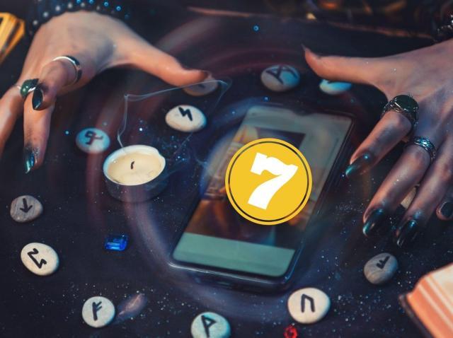 O masa pe care sunt puse rune si cifra 7, se observa si doua maini cu unghiile negre