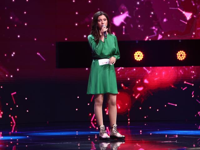 """Andra Barangă, într-o rochie verde, interpretând melodia  """"Run To You"""""""