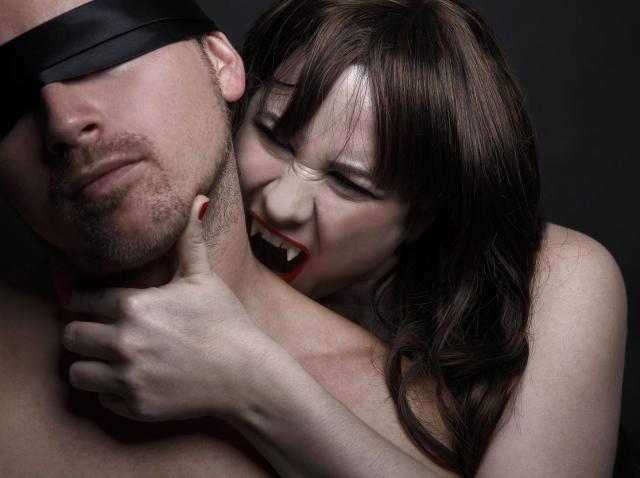 Un barbat legat la ochi și o femeie cu colți de vampiri