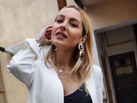 Flavia, îmbrăcată într-un costum alb, care îi pune în valoare silueta
