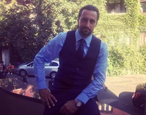 Denis Ștefan îmbracat într-o cămașă albastră, cravata neagră și pantalon negri. Stă jos și se observă în fotografie și pomi înverziți.