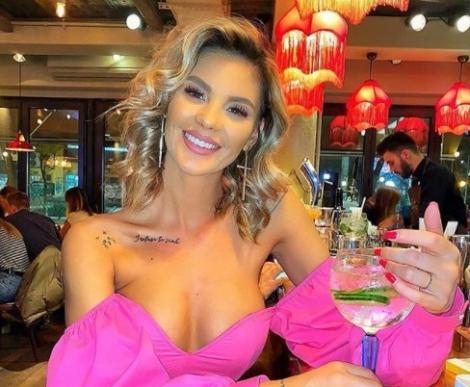 Ramona Olaru, zâmbește. Este îmbrăcată într-o bluză roz și cu umerii dezgoliți, ține un pahar în mână și are multe accesorii.