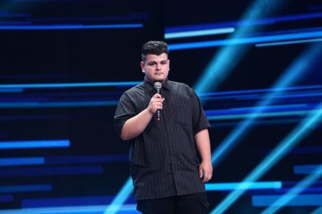 Mihai Tasici pe scena Iumor, imbracat intr-o camasa neagra si pantaloni negrii