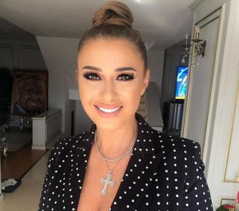 Anamaria Prodan intr-un sacou sexy, cu bustul generos la vedere. Impresara zambeste la camera