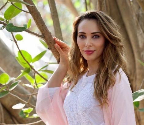 Iulia Vantur intr-o bluza alba, langa un copac