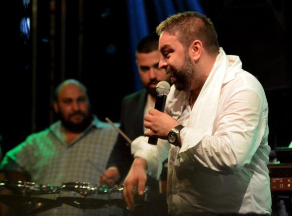 Florin Salam, într-o cămașă albă, la o cântare din 2017