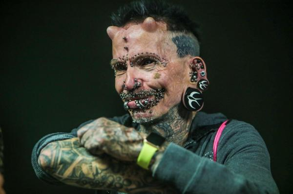 Rolf Buchholz, fotografiat in timp ce se uita in partea stanga si zambeste atat cat ii permit sutele de piercing-uri