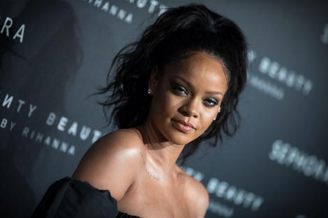 Rihanna, îmbrăcată într-o rochie neagră, cu ochii puternic conturați și părul prins într-o coadă în vârful capului