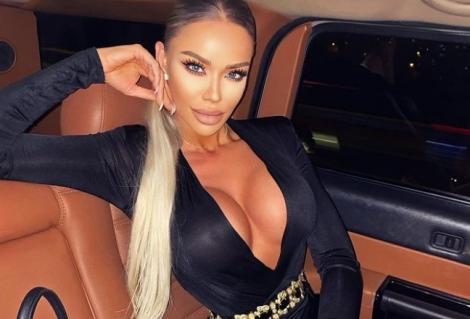 Bianca Drăgușanu în mașină, îmbrăcată într-o rochie neagră, mulată și cu decolteu generos
